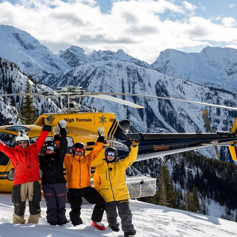 friends standing in front of Stellar heliski helicopter